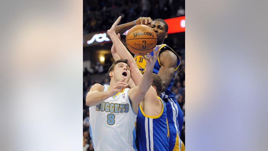 Denver Nuggets forward Danilo Gallinari, left, of Italy, puts up a shot over Golden State Warriors forward David Lee, right, and center Festus Ezeli, top, in the second half of an NBA basketball game on Sunday, Jan. 13, 2013, in Denver. The Nuggets won 116-105. (AP Photo/Chris Schneider)