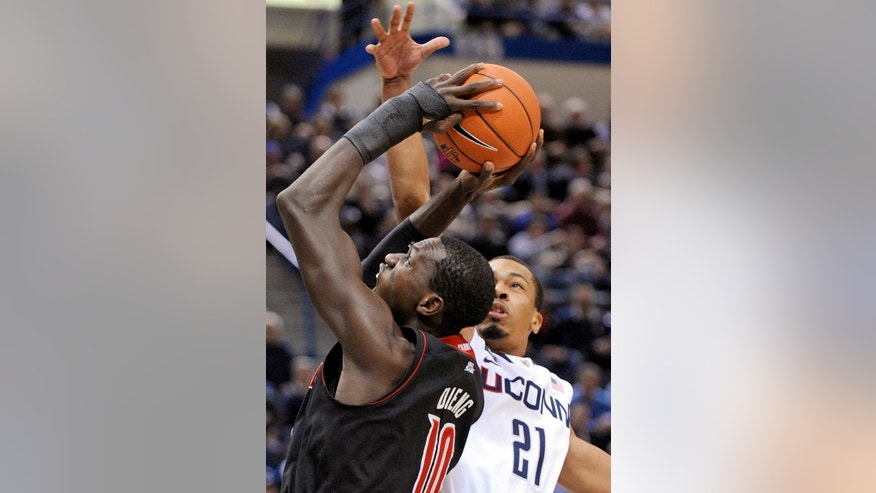 Louisville's Gorgui Dieng, left, is guarded by Connecticut's Omar Calhoun during the first half of an NCAA college basketball game in Hartford, Conn., Monday, Jan. 14, 2013. (AP Photo/Fred Beckham)