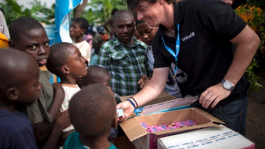 June 6, 2011: Rory McIlroy distributes bars of soap to children at a kindergarten run by UNICEF in Port-au-Prince, Haiti. (AP)
