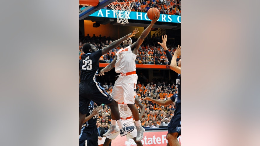 Syracuse's C. J. Fair scores against Villanova's Daniel Ochefu,left, during the second half of an NCAA college basketball game in Syracuse, N.Y., Saturday, Jan. 12, 2013. Syracuse won 72-61. (AP Photo/Kevin Rivoli)