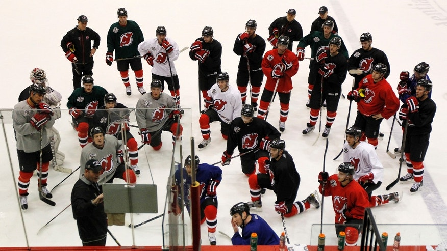New Jersey Devils head coach Peter DeBoer, bottom left, writes on a board during the team's first official practice since the NHL hockey lockout ended, Sunday, Jan. 13, 2013, in Newark, N.J. (AP Photo/Julio Cortez)