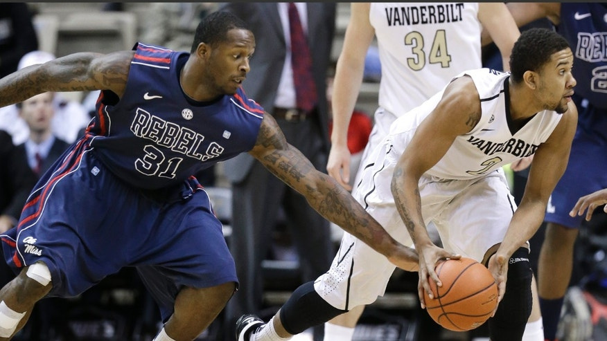 Mississippi forward Murphy Holloway (31) reaches for the ball controlled by Vanderbilt guard Kedren Johnson (2) in the first half of an NCAA college basketball game on Tuesday, Jan. 15, 2013, in Nashville, Tenn. (AP Photo/Mark Humphrey)