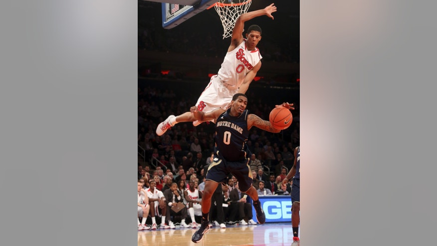 St. John's Jamal Branch, top, fouls Notre Dame's Eric Atkins during the first half of an NCAA college basketball game, Tuesday, Jan. 15, 2013, at Madison Square Garden in New York.