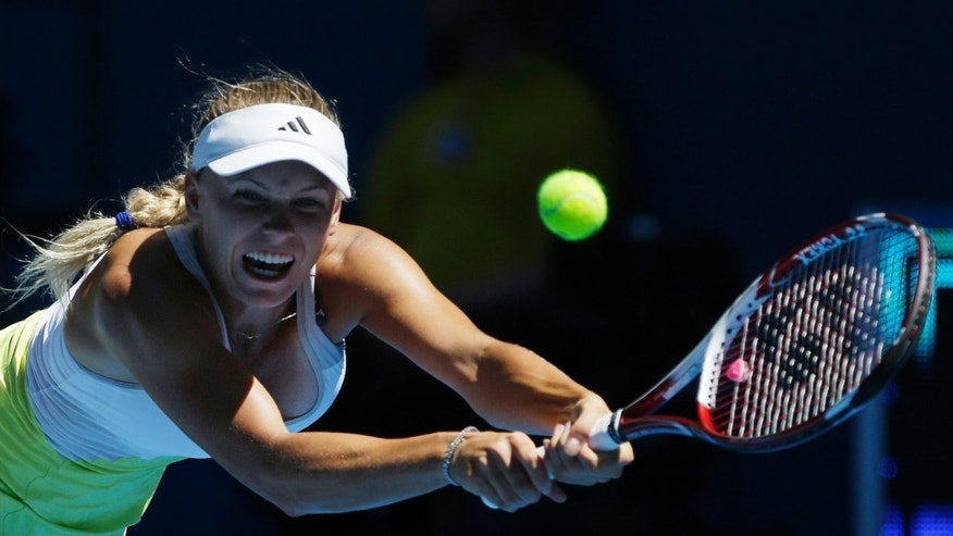 Denmark's Caroline Wozniacki hits backhand return to Germany's Sabine Lisicki during their first round match at the Australian Open tennis championship in Melbourne, Australia, Tuesday, Jan. 15, 2013. (AP Photo/Rob Griffith)