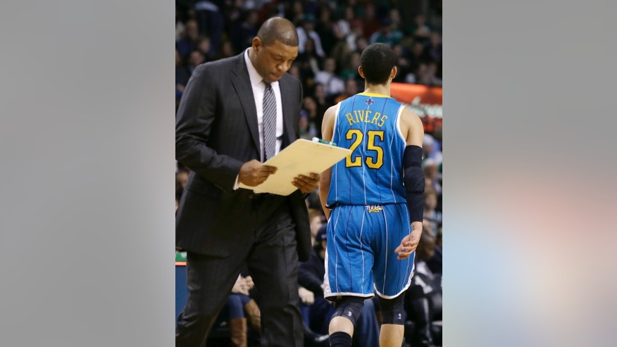 Boston Celtics head coach Doc Rivers, left, looks at his clipboard as his son, New Orleans Hornets shooting guard Austin Rivers (25), walks toward his bench late in the fourth quarter of an NBA basketball game in Boston, Wednesday, Jan. 16, 2013. The Hornets won 90-78. (AP Photo/Elise Amendola)
