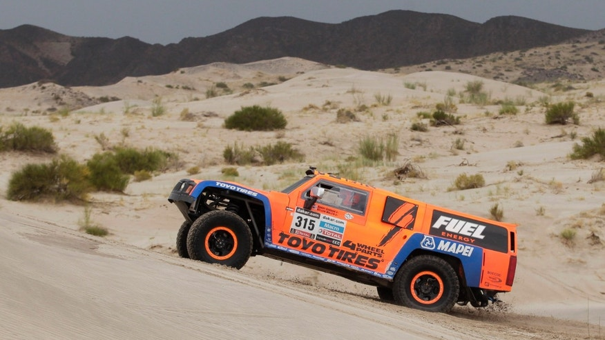 Robby Gordon and co-driver Kellon Walch of the U.S. races across the dunes during the 11th stage of the 2013 Dakar Rally from La Rioja to Fiambala, Argentina, Wednesday, Jan. 16, 2013. The race finishes in Santiago, Chile, on Jan. 20. (AP Photo/Victor R. Caivano)