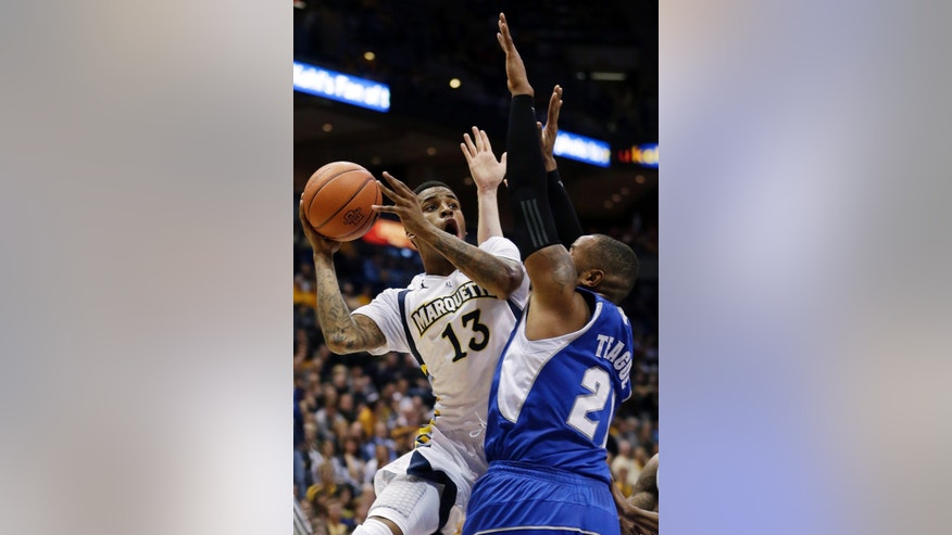 Marquette's Vander Blue (13) shoots over Seton Hall's Eugene Teague (21) during the first half of an NCAA college basketball game Wednesday, Jan. 16, 2013, in Milwaukee. (AP Photo/Morry Gash)