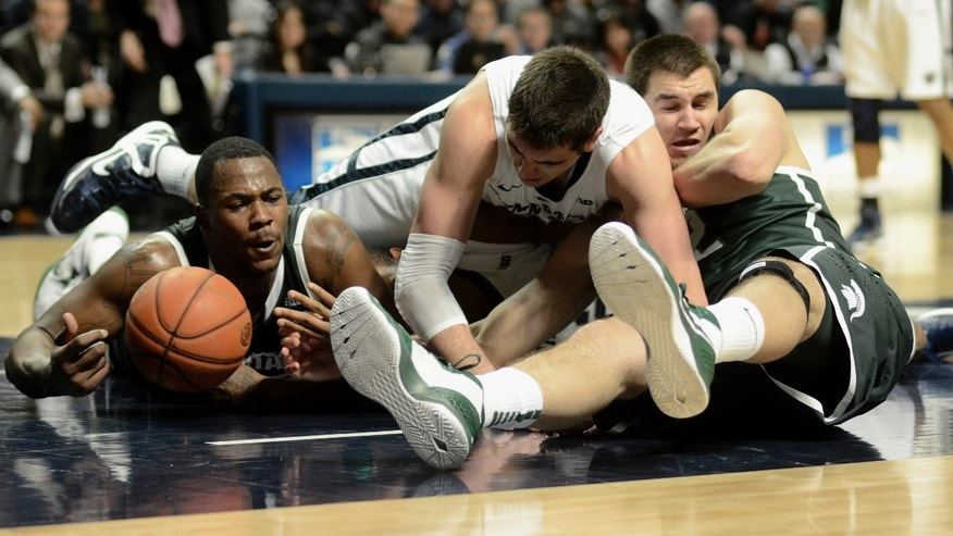 Michigan State's Derrick Nix, left, and Alex Gauna, right, struggle for a loose ball with Penn State's Sasa Borovnjak, center, during the first half of an NCAA college basketball game in State College, Pa., Wednesday, Jan. 16, 2013. (AP Photo/Ralph Wilson)