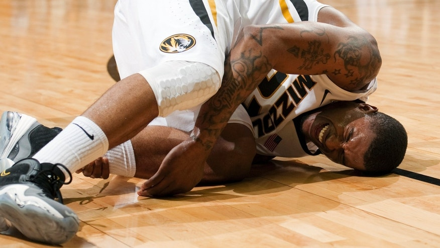 Missouri's Earnest Ross grabs his ankle in pain as he falls to the court during the first half of an NCAA college basketball game against Georgia, Wednesday, Jan. 16, 2013, in Columbia, Mo. Ross went to the locker room after the injury. (AP Photo/L.G. Patterson)