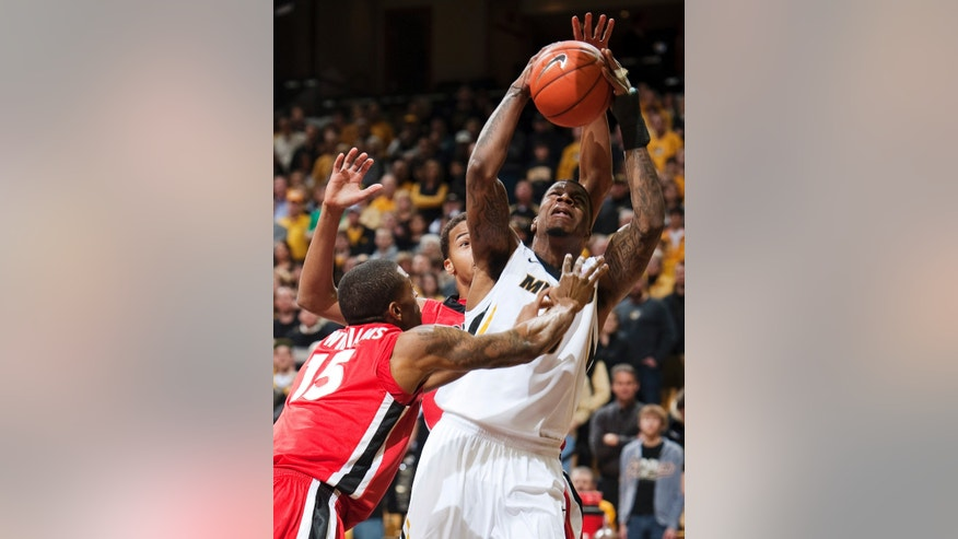 Missouri's Tony Criswell, right, shoots between Georgia's Donte' Williams, left, and Tim Dixon during the first half of an NCAA college basketball game, Wednesday, Jan. 16, 2013, in Columbia, Mo. (AP Photo/L.G. Patterson)