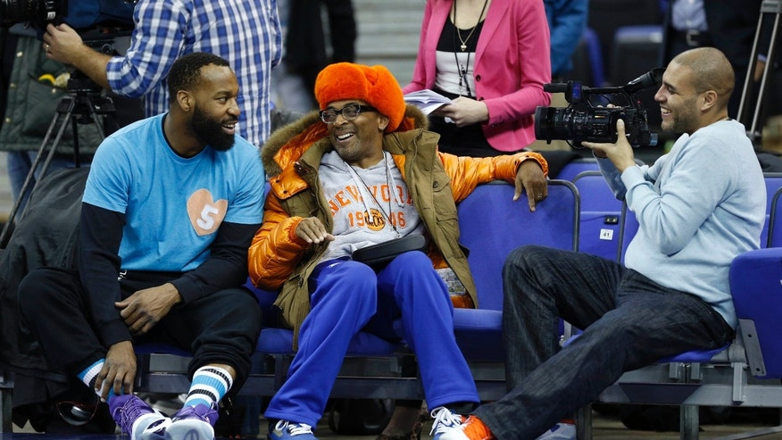 "U.S. movie director and New York Knicks fan Spike Lee, center, speaks to former Knicks player Baron Davis, left, as they watch a Knicks training session at the 02 arena in London, Wednesday, Jan. 16, 2013.  The Detroit Pistons are due to play a ""home"" NBA league game against the New York Knicks at the arena on Thursday.  (AP Photo/Matt Dunham)"