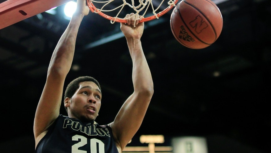 Purdue's D.J. Byrd (21) drives to the basket against Nebraska's Shavon Shields (31) and David Rivers, right, in the first half of their NCAA college basketball game in Lincoln, Neb., Wednesday, Jan. 16, 2013. (AP Photo/Nati Harnik)