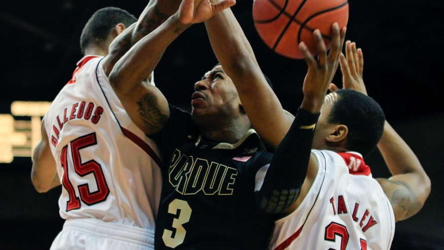 Purdue's Ronnie Johnson (3) drives against Nebraska's Ray Gallegos (15) and Dylan Talley (24) in the first half of their NCAA college basketball game in Lincoln, Neb., Wednesday, Jan. 16, 2013. (AP Photo/Nati Harnik)