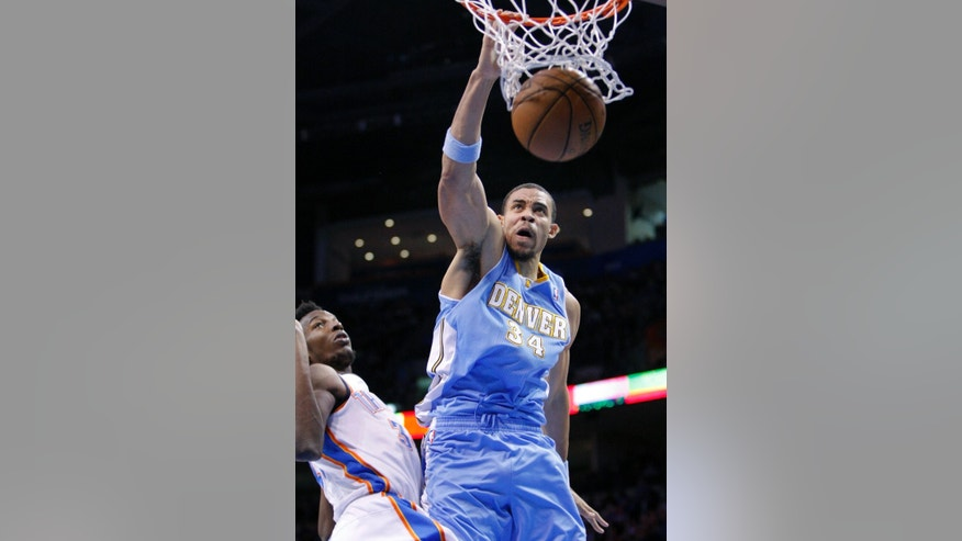 Denver Nuggets center JaVale McGee, right, dunks the ball in front of Oklahoma City Thunder's Hasheem Thabeet, left, during the first quarter of an NBA basketball game in Oklahoma City, Wednesday, Jan. 16, 2013.  (AP Photo/Alonzo Adams)