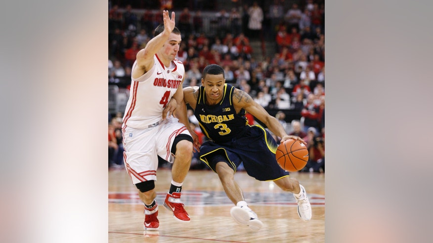 Ohio State's Aaron Craft (4) stays close to Michigan's Trey Burke during the second half of an NCAA college basketball game Sunday, Jan. 13, 2013, in Columbus, Ohio. Ohio State won 56-53. (AP Photo/Mike Munden)