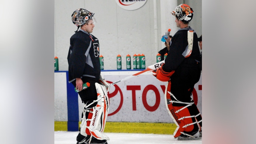 Philadelphia Flyers goalies Ilya Bryzgalov, left, and Michael Leighton take a break during the first hockey practice session at the team's training camp on Sunday, Jan. 13, 2013, in Voorhees, N.J. The Flyers and other NHL teams returned after a nearly four-month-old lockout ended with a settlement on a new collective bargaining agreement. (AP Photo/Tom Mihalek)