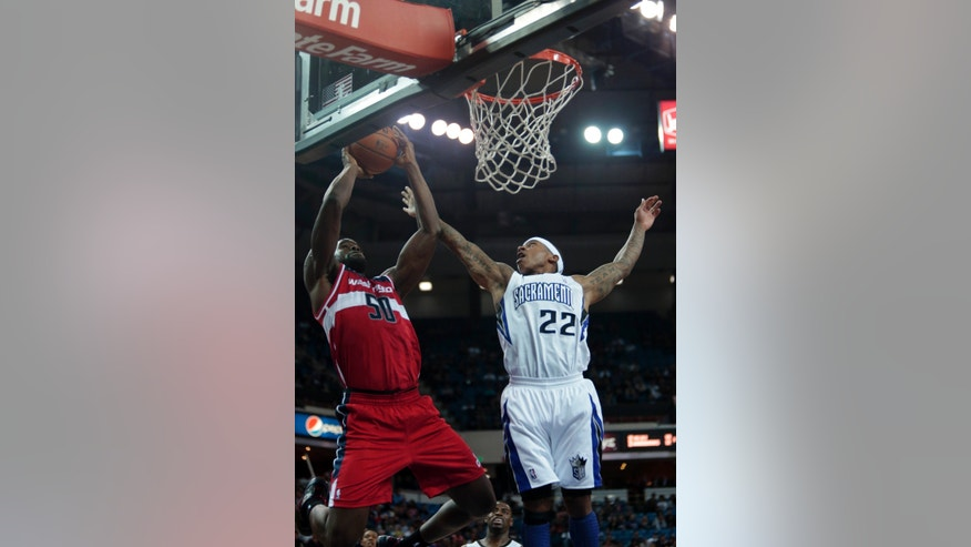 Washington Wizards center Emeka Okafor, left, shoots over Sacramento Kings guard Isaiah Thomas during the second quarter of an NBA basketball game in Sacramento, Calif., Wednesday, Jan. 16, 2013. (AP Photo/Rich Pedroncelli)