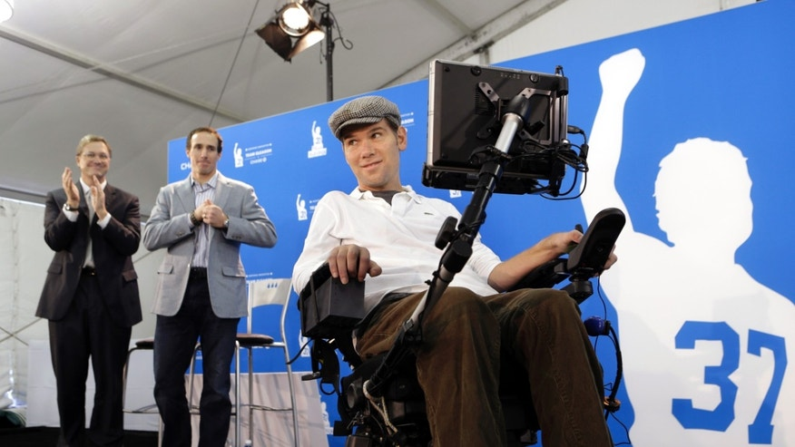 Steve Gleason, right, a former New Orleans Saints NFL football special teams standout who was diagnosed with amyotrophic lateral sclerosis, demonstrates the newest technology for Team Gleason House, a residence he is creating for up to 18 people with ALS and multiple sclerosis, during a news conference, Thursday, Jan. 17, 2013, in New Orleans. Work is still being done at the residence, which will make up the first floor of a 116-bed skilled nursing facility being developed by the St. Margaret's Daughters order in a mid-city hospital abandoned after the floods of Hurricane Katrina. Behind him is Saints quarterback Drew Brees, second from left, and Todd Maclin, of Chase Bank, which gave $350,000 to install the system made by Promixis LLC of Jupiter, Fla. (AP Photo/Gerald Herbert)