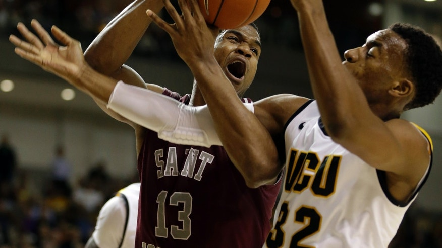 Saint Joseph's forward Ronald Roberts Jr. (13) and Virginia Commonwealth guard Melvin Johnson (32) struggle for a rebound during the second half of an NCAA college basketball game on Thursday, Jan. 17, 2013, in Richmond, Va. VCU won 92-86.  (AP Photo/Steve Helber)