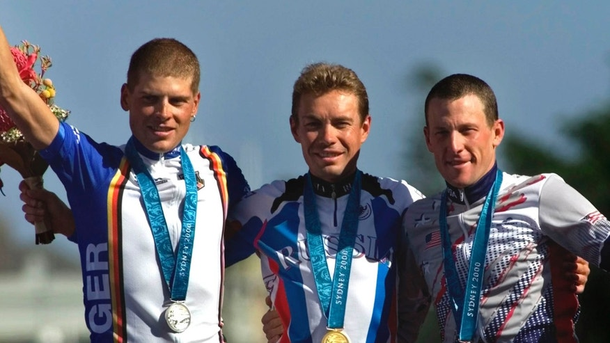 Sept. 30, 2000: In this file photo Russia's Viacheslav Ekimov, center, winner of the gold medal in the men's individual time trials, celebrates with Germany's silver medal winner Jan Ullrich, left, and U.S bronze medal winner Lance Armstrong at the cycling road course in Sydney, for the Summer Olympic Games.