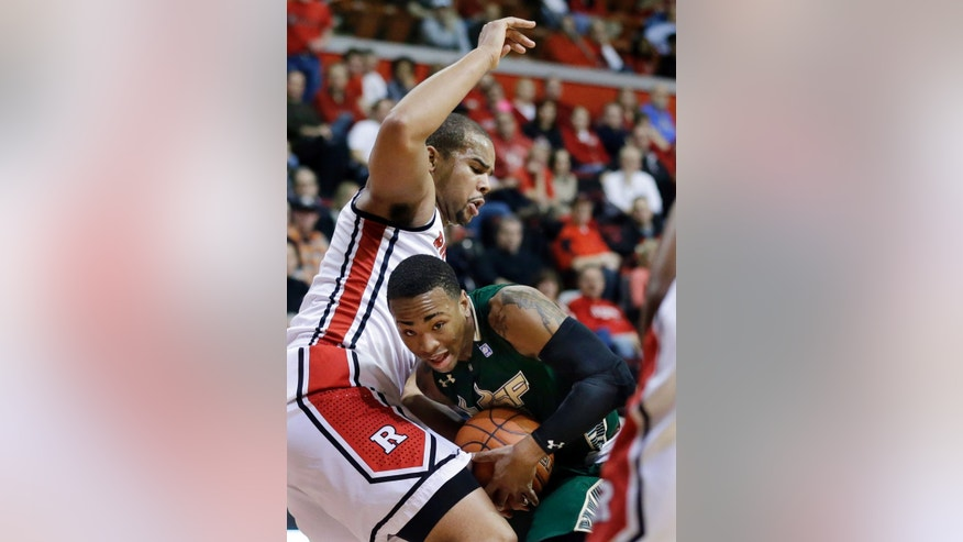 South Florida's Anthony Collins (11) tries to hold onto the ball as Rutgers' Austin Johnson (21) blocks his path during the first half of an NCAA college basketball game, Thursday, Jan. 17, 2013, in Piscataway, N.J. (AP Photo/Mel Evans)