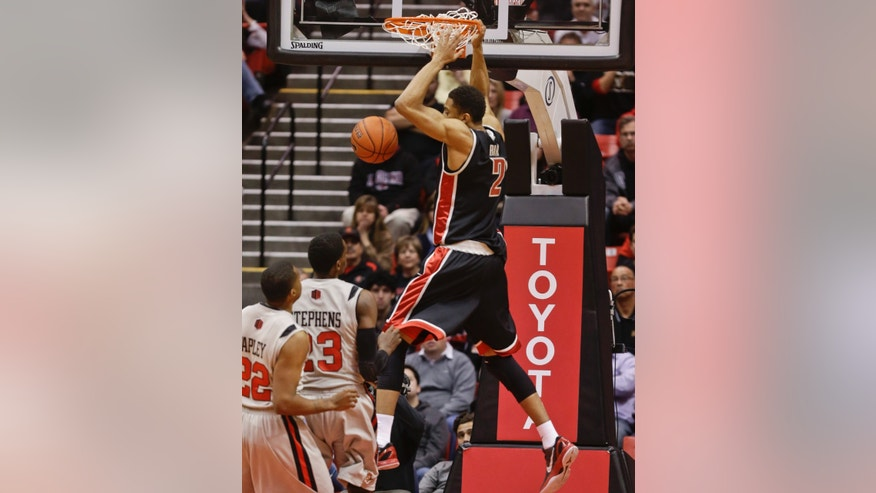 UNLV forward Khem Birch. top, dunks over San Diego State defenders during the first half of an NCAA college basketball game on Wednesday Jan. 16, 2013, in San Diego. (AP Photo/Lenny Ignelzi)
