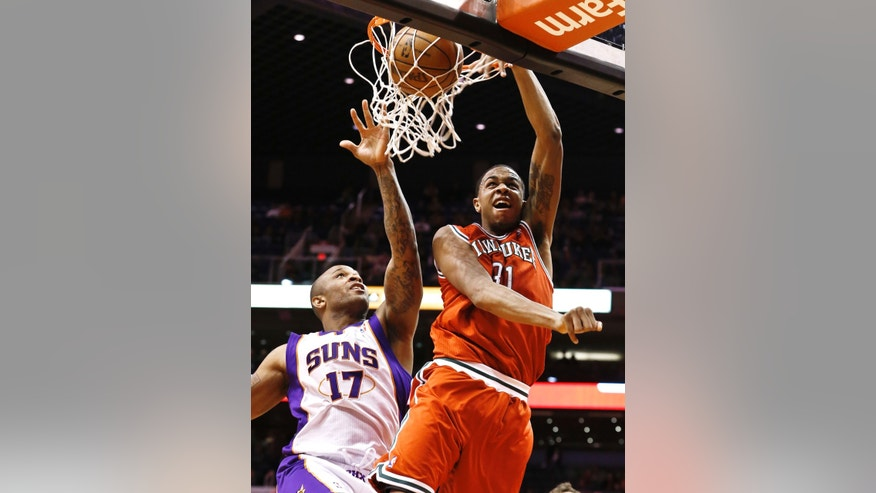 Milwaukee Bucks' John Henson (31) dunks as Phoenix Suns' P.J. Tucker (17) tries to defend in the first half during an NBA basketball game on Thursday, Jan. 17, 2013, in Phoenix. (AP Photo/Ross D. Franklin)
