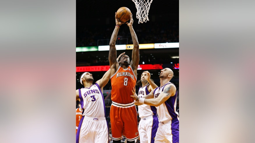 Milwaukee Bucks' Larry Sanders (8) scores against Phoenix Suns' Jared Dudley (3), Marcin Gortat, right, of Poland, and Luis Scola, of Argentina, in the first half during an NBA basketball game on Thursday, Jan. 17, 2013, in Phoenix. (AP Photo/Ross D. Franklin)