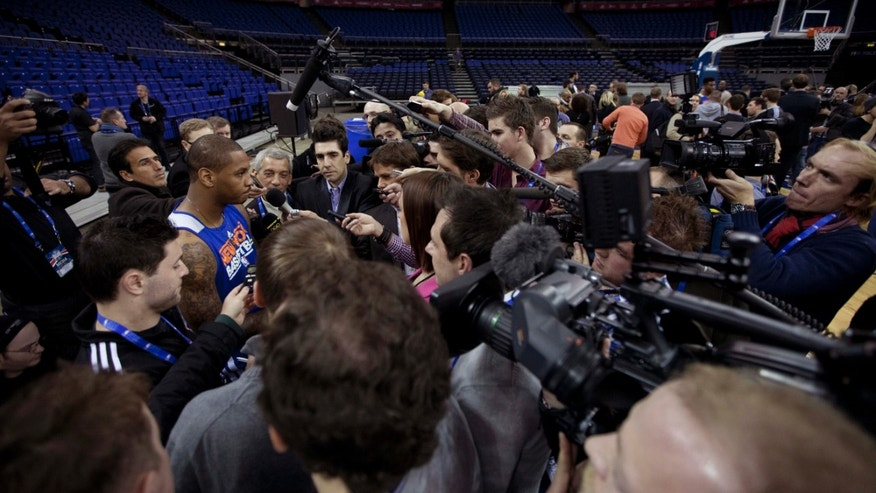 "New York Knicks forward Carmelo Anthony, at left, is surrounded by members of the media as he speaks before the start of a training session at the 02 arena in London, Wednesday, Jan. 16, 2013.  The Detroit Pistons are due to play a ""home"" NBA league game against the New York Knicks at the arena on Thursday.  (AP Photo/Matt Dunham)"