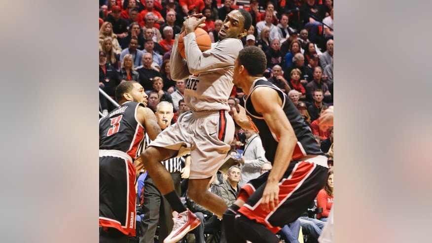 San Diego State guard Jamaal Franklin, center, covers the ball as he tries to penetrate the UNLV defense during the first half of an NCAA college basketball game on Wednesday Jan. 16, 2013, in San Diego. (AP Photo/Lenny Ignelzi)