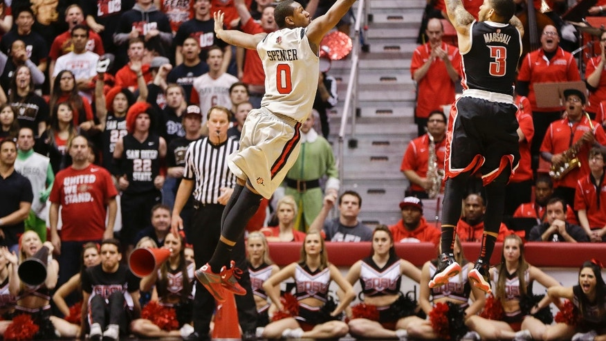 UNLV guard Anthony Marshall lets fly a jumper over San Diego State forward Skylar Spencer during the second half of UNLV's 82-75 victory in a NCAA college basketball game Wednesday Jan. 16, 2013 in San Diego. Marshall led UNLV with  20 points.  (AP Photo/Lenny Ignelzi)