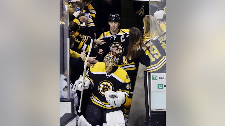 Fans reach out to Boston Bruins captain Zdeno Chara (33) and goaltender Tuukka Rask (40) as they take the ice for an NHL hockey scrimmage against the Providence Bruins at TD Garden in Boston, Tuesday, Jan. 15, 2013. (AP Photo/Elise Amendola)