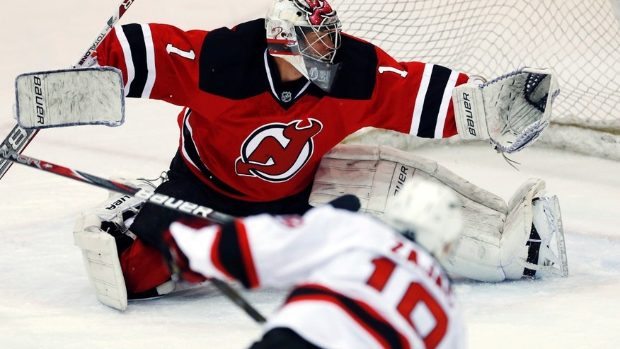 New Jersey Devils goalie Johan Hedberg (1), of Sweden, is unable to stop a shot by Devils center Travis Zajac (19) during an NHL hockey scrimmage against the Albany Devils, the team's AHL affiliate, Wednesday, Jan. 16, 2013, in Newark, N.J. (AP Photo/Julio Cortez)