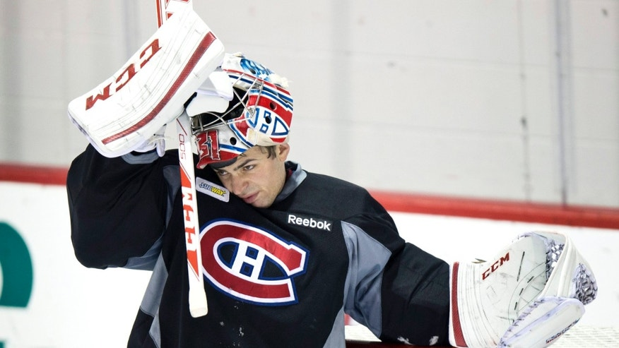 Montreal Canadiens goaltender Carey Price slips on his face mask during NHL hockey practice, Tuesday, Jan. 15, 2013, in Brossard, Quebec. (AP Photo/The Canadian Press, Paul Chiasson)