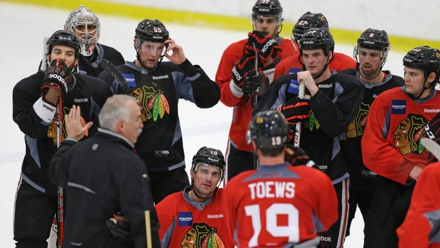 Chicago Blackhawks head coach Joel Quenneville, bottom left, speaks to his team during NHL hockey practice, Monday, Jan. 14, 2013, in Chicago. The Blackhawks are scheduled to begin their lockout-shortened, 48-game regular season against the Los Angeles Kings on Saturday in Los Angeles. (AP Photo/M. Spencer Green)