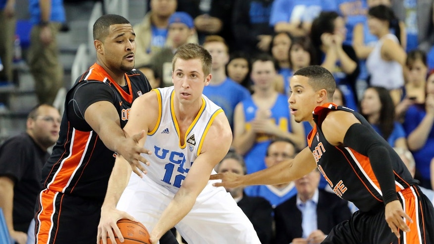 Oregon State center/forward Joe Butler (11), left and guard Challe Barton (4), of Sweden, defend  UCLA guard David Wear in the first half of an NCAA college basketball game in Los Angeles, Thursday, Jan. 17, 2013. (AP Photo/Reed Saxon)