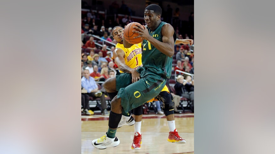 Oregon's Damyean Dotson is defended by Southern California's Jio Fontan (1) during the first half of an NCAA college basketball game in Los Angeles, Thursday, Jan. 17, 2013. (AP Photo/Jae C. Hong)