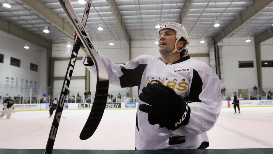 Dallas Stars left wing Brenden Morrow trades out a hockey stick during NHL hockey training camp in Frisco, Texas, Tuesday, Jan. 15, 2013. (AP Photo/LM Otero)