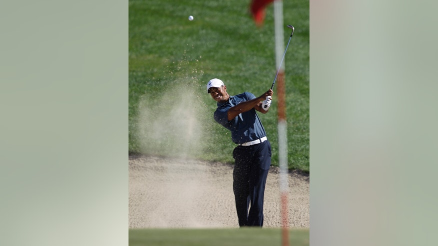Tiger Woods from the U.S. plays a bunker shot on the 7th hole during the second round of Abu Dhabi Golf Championship in Abu Dhabi, United Arab Emirates, Friday, Jan. 18, 2013. (AP Photo/Kamran Jebreili)