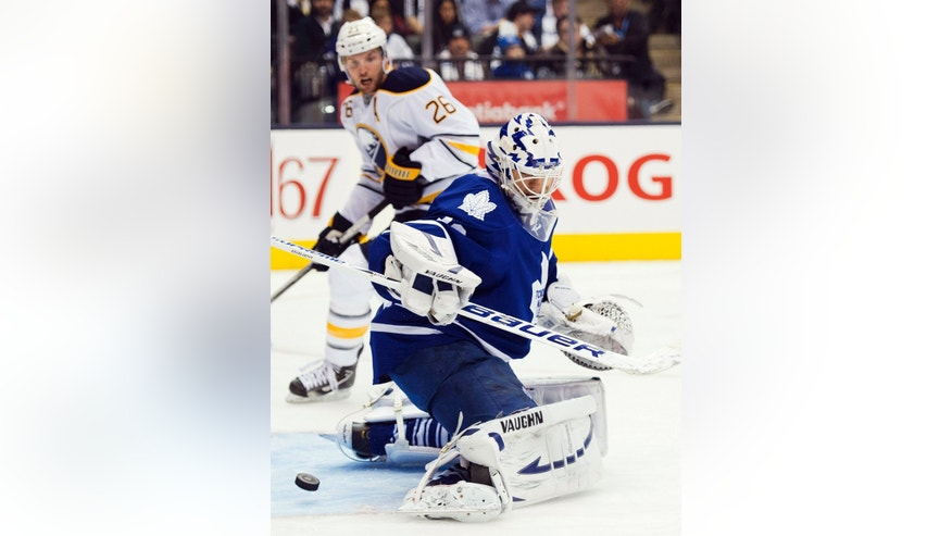 Toronto Maple Leafs goalie Ben Scrivens, right, looks back for the loose puck as Buffalo Sabres forward Thomas Vanek, center, watches during the third period of their NHL hockey game, Monday, Jan. 21, 2013, in Toronto. The Sabres won 2-1. (AP Photo/The Canadian Press, Nathan Denette)