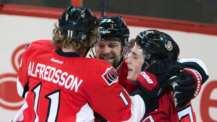 Ottawa Senators center Kyle Turris, right, is congratulated by right wing Daniel Alfredsson, left, and Guillaume Latendresse following a goal during the second period of an NHL hockey game against the Florida Panthers in Ottawa, Ontario, Monday, Jan. 21, 2013. (AP Photo/The Canadian Press, Adrian Wyld)