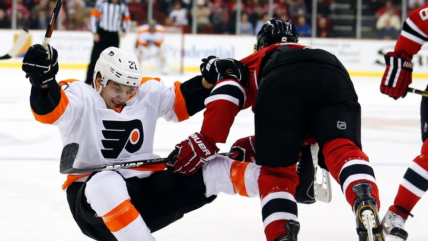 Philadelphia Flyers center Scott Laughton, left, is knocked to the ice by New Jersey Devils defenseman Andy Greene during the first period of an NHL hockey game, Tuesday, Jan. 22, 2013, in Newark, N.J. (AP Photo/Julio Cortez)