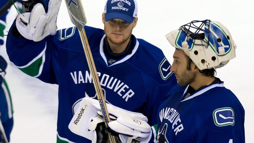 Vancouver Canucks' goalie Cory Schneider, left, and goalie Roberto Luongo acknowledge the crowd after the team's 7-3 loss to the Anaheim Ducks in an NHL hockey game in Vancouver, British Columbia, on Saturday, Jan. 19, 2013. (AP Photo/The Canadian Press, Darryl Dyck)