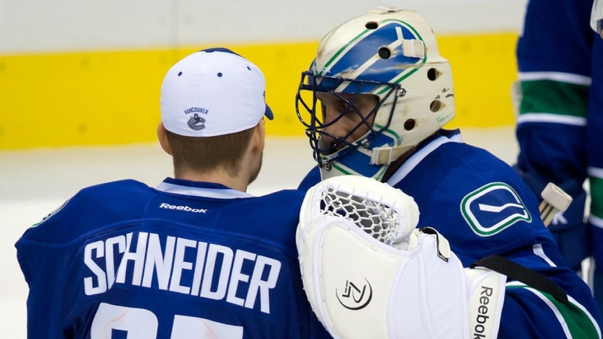 Vancouver Canucks' goalie Cory Schneider, left, and goalie Roberto Luongo talk after the team's 7-3 loss to the Anaheim Ducks in an NHL hockey game in Vancouver, British Columbia on Saturday, Jan. 19, 2013. (AP Photo/The Canadian Press, Darryl Dyck)