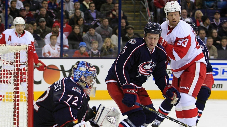 Columbus Blue Jackets' Sergei Bobrovsky, of Russia, makes a save as teammate and countryman Nikita Nikitin, center, and Detroit Red Wings' Johan Franzen, of Sweden, wait for a rebound during the first period of an NHL hockey game Monday, Jan. 21, 2013, in Columbus, Ohio. (AP Photo/Jay LaPrete)