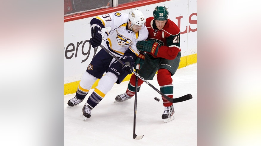 Nashville Predators center Colin Wilson (33) and Minnesota Wild defenseman Ryan Suter (20) battle for possession during the first period of an NHL hockey game Tuesday, Jan. 22, 2013 in St. Paul, Minn. (AP Photo/Genevieve Ross)