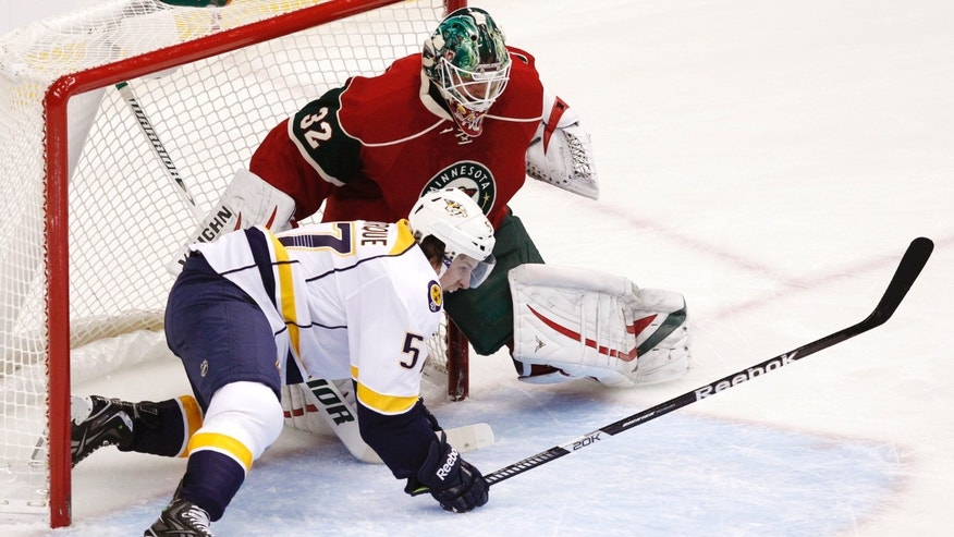 Nashville Predators left wing Gabriel Bourque (57) slides into Minnesota Wild goalie Niklas Backstrom (32), of Finland, after attempting to score during the first period of an NHL hockey game Tuesday, Jan. 22, 2013 in St. Paul, Minn. (AP Photo/Genevieve Ross)