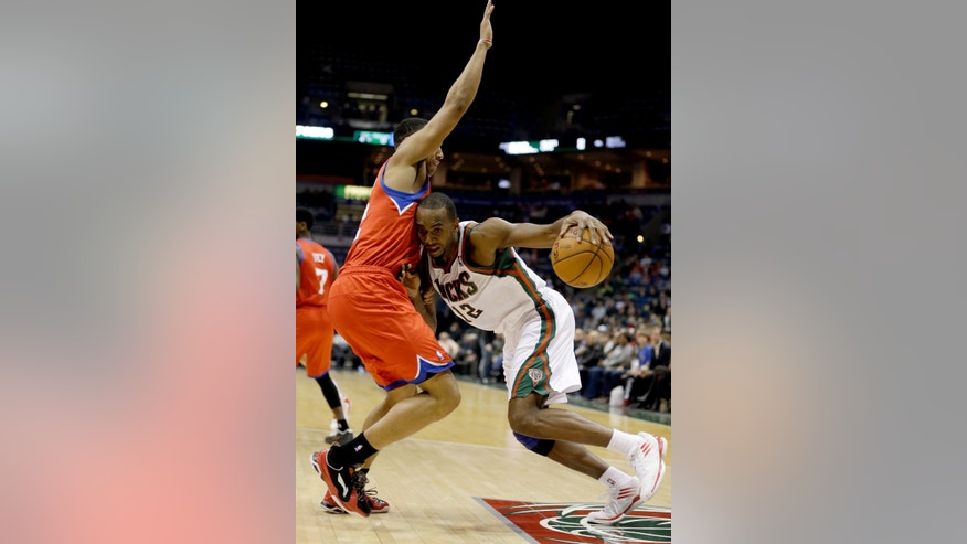 Milwaukee Bucks' Luc Richard Mbah a Moute, right, drives against Philadelphia 76ers' Evan Turner, left, during the second half of an NBA basketball game, Tuesday, Jan. 22, 2013, in Milwaukee. (AP Photo/Jeffrey Phelps)