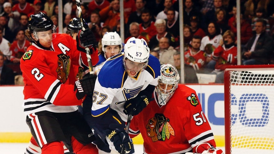 St. Louis Blues left wing David Perron (57) is unable to get a shot on goal as Chicago Blackhawks defenseman Duncan Keith (2) and goalie Corey Crawford defend during the first period of an NHL hockey game, Tuesday, Jan. 22, 2013, in Chicago. (AP Photo/Charles Rex Arbogast)