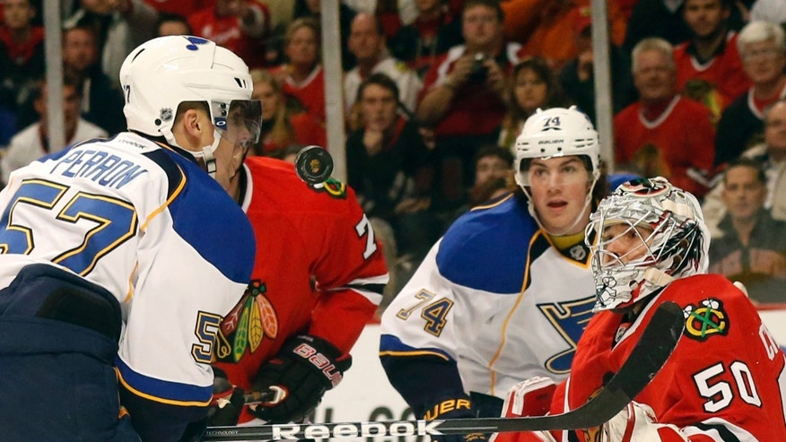 St. Louis Blues left wing David Perron (57), right wing T.J. Oshie (74) and Chicago Blackhawks goalie Corey Crawford watch the puck in during the first period of an NHL hockey game, Tuesday, Jan. 22, 2013, in Chicago. (AP Photo/Charles Rex Arbogast)
